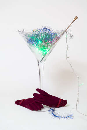 Invisible hands in red gloves hold a huge glass martini glass on a white background. A magic cocktail shines in it