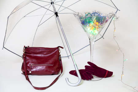 Invisible hands in red gloves hold a large martini glass from below. A magic cocktail glows inside the glass. There is a transparent umbrella over the glass. Nearby is a red women bag