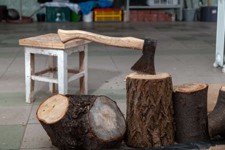 ax sticks out in a stump in the garage. There are stumps of different heights nearby Standard-Bild