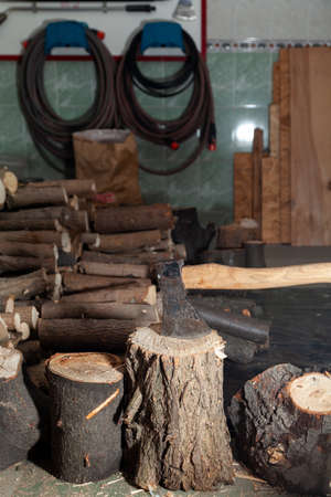 ax sticks out in a stump in the garage. In the background a pile of round firewood and a fire shield
