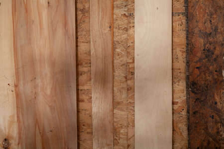 Plywood sheets of different widths lie on top of the pressed sawdust board and form vertical stripes Standard-Bild