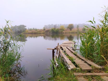 The old wooden pier goes into the lake. Around the green grass, the reeds. Russia.