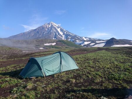Green tent stands on a field of green grass on the background of a snow-capped volcano. Kamchatka. Russia.