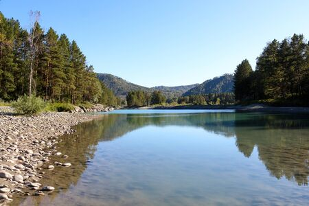 Landscape with reflection in the water. Transparent reservoir. Green trees, blue sky, pebble beach.