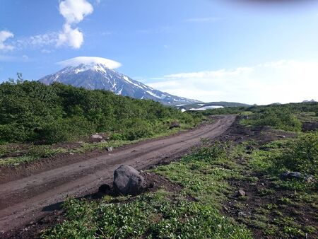 A muddy dry road leads to the volcano. Near the road stone. Green bushes, blue sky, white clouds. Kamchatka. Russia.