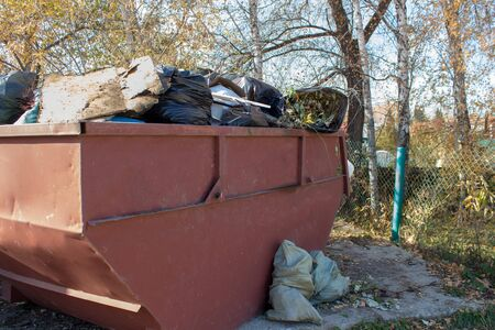 An iron garbage can of red color is overflowing with bags of tree branches and leaves. Overflowing with garbage. Stok Fotoğraf