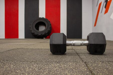 Dumbbell in the gym on the background of a large black tire. Crossfit. Stock fotó