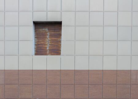 A wall of brown and light brown squares with a window.
