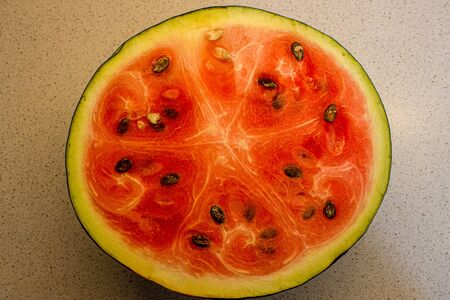 Half watermelon with a clearly structured pattern. Red ripe watermelon, black seeds.