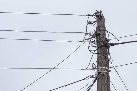 A wooden pole with electric wires against a gray sky. Stok Fotoğraf