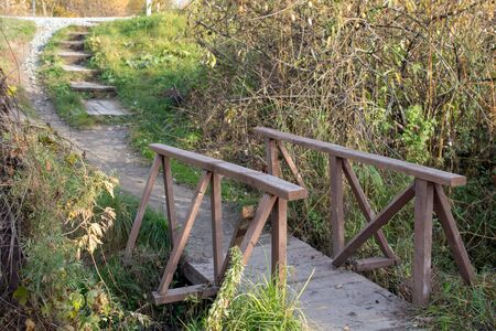 Wooden bridge with wooden railings across a small river, turning into a path with steps. Stock fotó