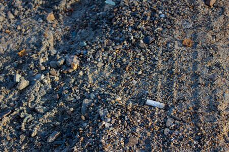 A cigarette butt of white color lies on the rocky Bank of the river. Environmental pollution, environmental disaster. Stock fotó - 132688207