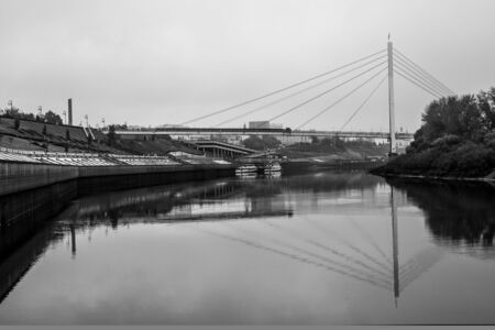 Pedestrian bridge over the river on the city background. River embankment. Stok Fotoğraf