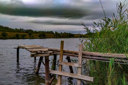 Old wooden pier on the lake. Around green the grasses. Far Bank with bushes. Cloudy weather. Gray Cumulus clouds.