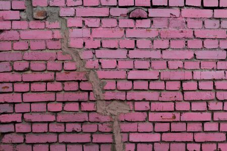 A brick wall of pink bricks with a crack across the wall.