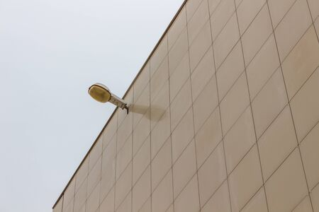 Street lamp on the wall of the building, against the gray sky. Stock fotó - 132615285