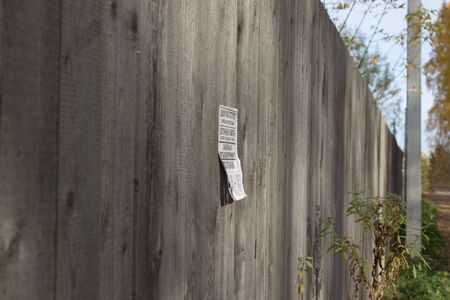 A paper ad with loose leaves is glued to a wooden fence in the countryside. In the background, a concrete pillar and blue sky.8