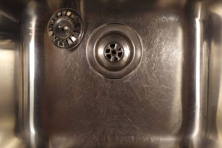 Shiny metal sink with a plug. Silver color. Scratch the surface. The view from the top. Stok Fotoğraf