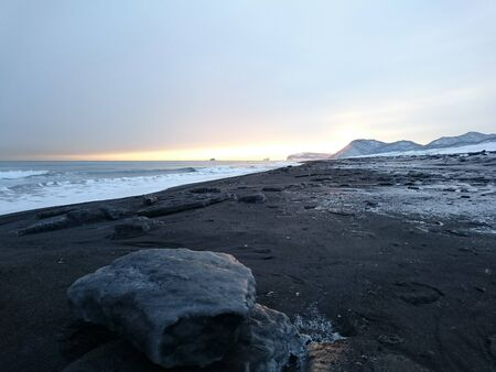 A piece of ice on the shore of the Pacific ocean on black sand. Mountains in the distance. Kamchatka. Russia. Stok Fotoğraf