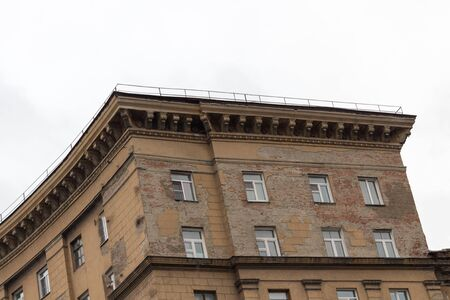 A semicircular building of brown brick against a gray sky. View from the end of the building. Stok Fotoğraf