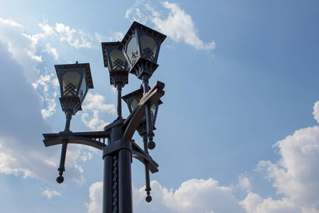 Street lamp in the ancient style on a background of blue sky with white clouds. Stok Fotoğraf
