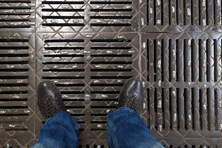 Legs in brown leather boots and dark blue jeans on a metal grille. Look from top to bottom.