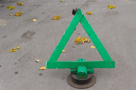 A green emergency stop sign stands on the asphalt. Next to the yellow leaves.