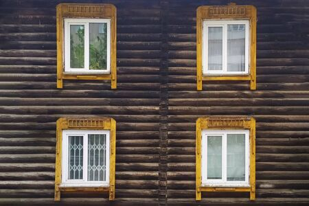 Wooden facade of the building with Windows. Wall of round timber. Stok Fotoğraf