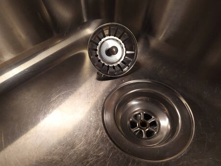 Shiny metal sink with a plug, close. Silver color. Scratch the surface. Diagonal view.
