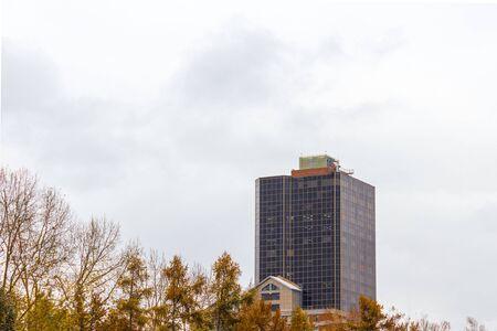 High-rise glazed building against the gray sky. Photo across the Park.