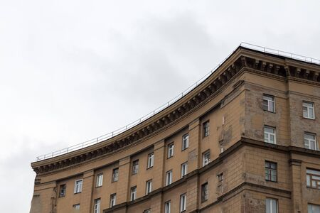 A semicircular building of brown brick against a gray sky. Stok Fotoğraf - 135026032