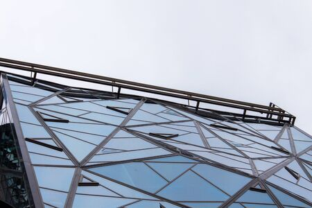 Glazed facade of the building of triangular pieces of glass. Bottom view. Stock fotó