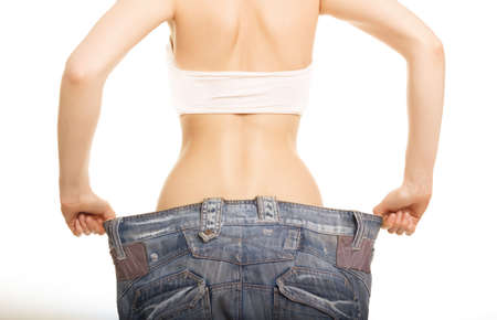 weight loss success: Photo of a young slim woman in oversized pair of old jeans Isolated on white Stock Photo