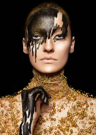 face paint: Ceremonial visage imagination Portrait of beauty woman in golden style with painted face Stock Photo