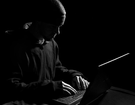 Silhouette of a hacker uses a command on graphic user interface Imagens - 30202489