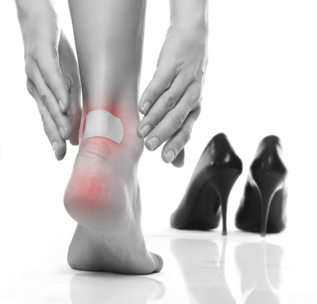 high heel shoes: female feet in pain after wearing high heeled shoes Stock Photo