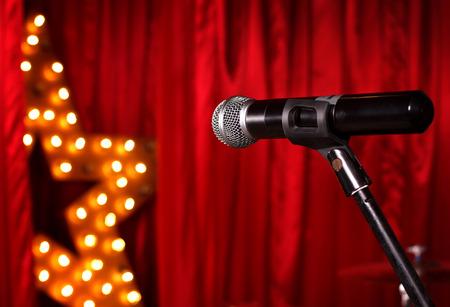microfono antiguo: micrófono en el escenario del teatro, la estrella de oro en el fondo con las cortinas rojas