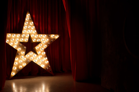 shows: Photo of golden star with light bulbs on red velvet curtain on stage Stock Photo