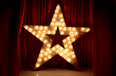 Photo of golden star with light bulbs on red velvet curtain on stage Stockfoto