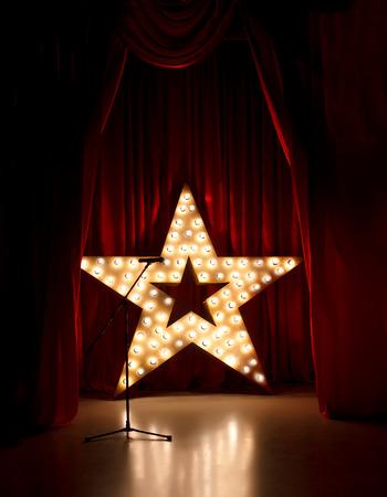 Micrófono en el escenario del teatro, estrella de oro con cortinas rojas alrededor