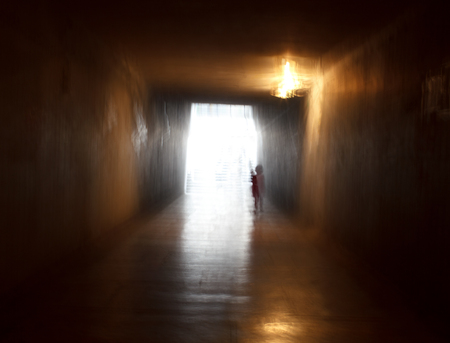 Ghost of are child in abstract tunnel.Light of the end of tunnel concept.Composition with blurred motion effect