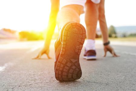 Atleet loper voeten lopen op de loopband close-up op shoe.Mans fitness met de zon effect op de achtergrond en open ruimte om hem heen