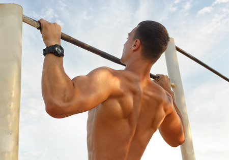 bar top: Closeup of strong  athlete doing pull-up on horizontal bar.Mans fitness with blue sky in the background and open space around him Stock Photo