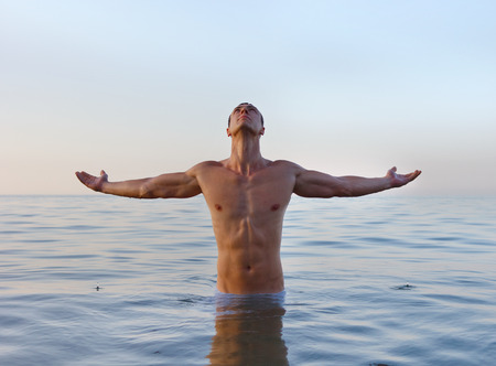 muscularity: Wide view of a sports man body figure in the sea with the blue sky in the background and open space around him