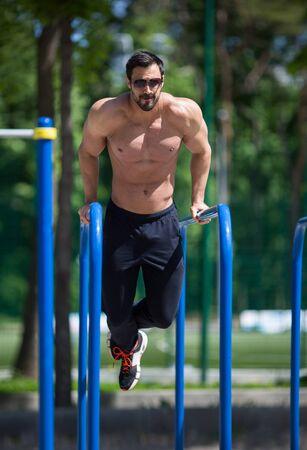 effort: athlete doing pull-up on horizontal bar.Mans fitness outdoor Stock Photo