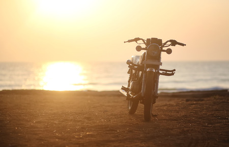 Motorcycle.Photo Motorcycle at sunset on a sandy beach in Goa, India.