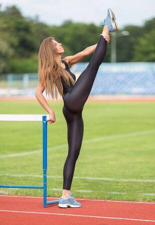 sportsmen: Sexy fitness.Warming-up.Athlete doing exercises at stadium