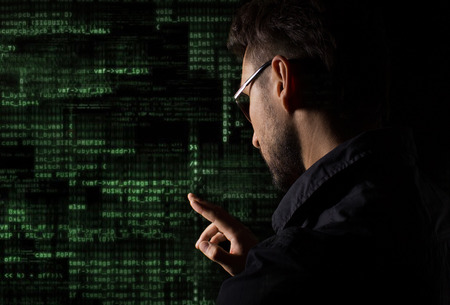 Silhouette of a hacker with graphic user interface around Stock Photo