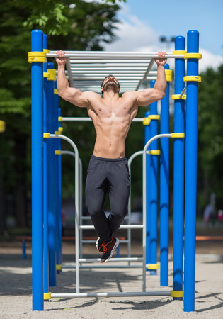 gripping bars: athlete doing pull-up on horizontal bar.Mans fitness outdoor Stock Photo