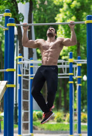 athlete doing pull-up on horizontal bar.Mans fitness outdoor Stock Photo